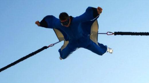 Un homme vole accroché au simulateur de chute libre